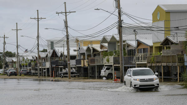 The storm surge from Tropical Storm Barry started pushing water into areas around Lake Pontchartrain Friday, as the storm slowly moved toward shore. Here, an SUV travels down Breakwater Drive near the Orleans Marina in New Orleans. The area is behind a flood wall that protects the rest of the city.