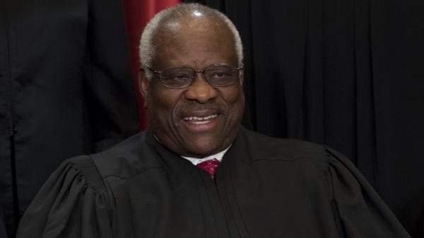 Justice Clarence Thomas sits for an official photo with other members of the Supreme Court.
