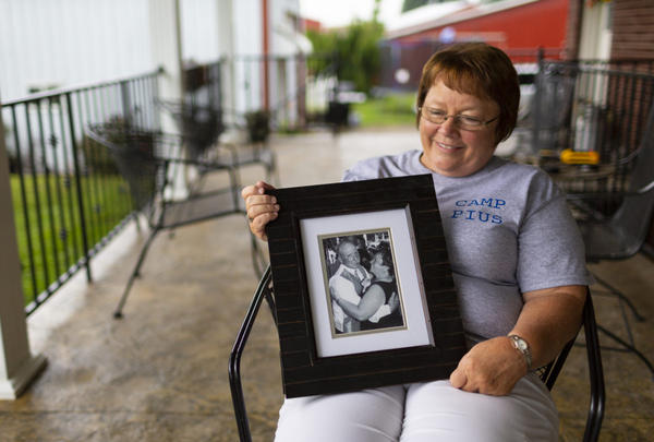 "Lisa Hobbs holds a picture of her husband, Gene ""Pius"" Hobbs."