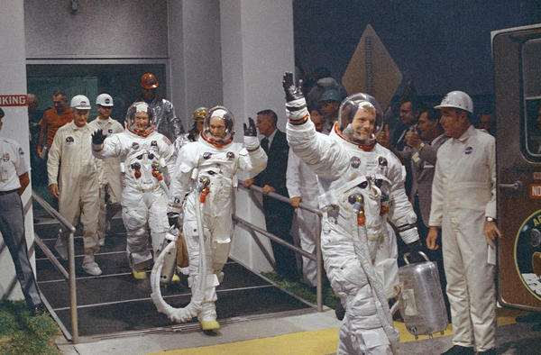 In this July 16, 1969 file photo, Neil Armstrong, waving in front, heads for the van that will take the crew to the rocket for launch to the moon at Kennedy Space Center.