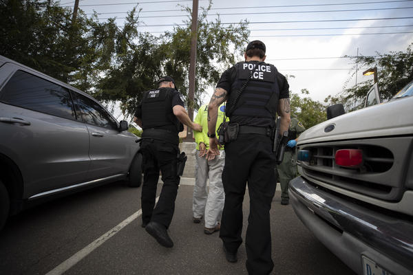 In this July 8, 2019, photo, a U.S. Immigration and Customs Enforcement (ICE) officers escort a man in handcuffs during an operation in Escondido, Calif.