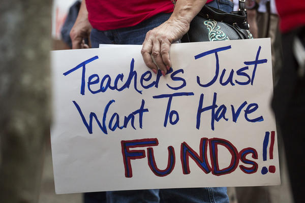 Teachers rally for a pay raise at the Austin Independent School District headquarters in May.