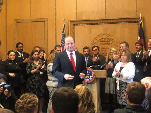 Gov. Jared Polis hands out the pens he used to sign Senate Bill 181. Conservatives who are trying to recall him say his signing of the oil and gas bill is one of the reasons they want to remove him from office.