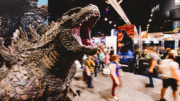 Godzilla — who's celebrating his own 65th birthday this year — watches over convention-goers on preview night at San Diego Comic Con.