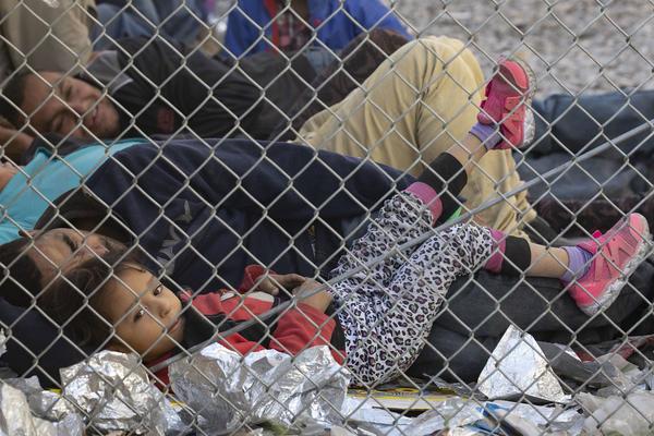 Migrants detained by Border Patrol are held in a fenced-off area below the Paso del Norte International Bridge in El Paso in March.
