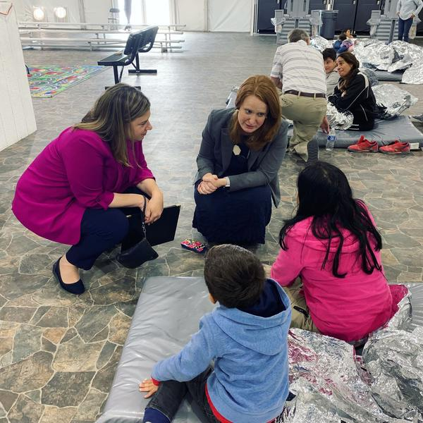 Rep. Elissa Slotkin and her deputy chief of staff Danielle Most talk to two children at a CBP holding facility in Donna, Texas.