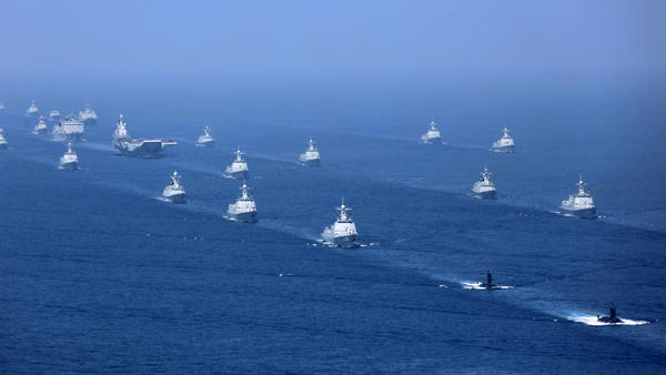 An April 2018 file photo released by China's Xinhua News Agency shows the Liaoning aircraft carrier accompanied by navy frigates and submarines conducting exercises in the South China Sea.