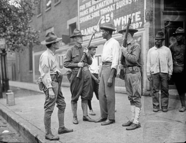 Armed National Guards and African American men standing on a sidewalk during the race riots in Chicago, Illinois, 1919.