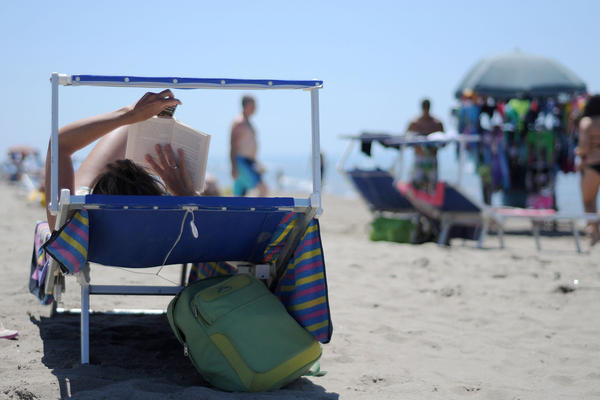 A sunbather reads on a private beach in Fiumicino, near Rome, on July 18, 2012. (Gabriel Bouys/AFP/GettyImages)