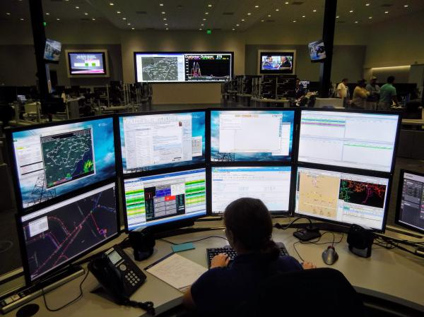 Control Center operators have a desk with eight screens showing information about power outages and line crews dispatched for repairs.