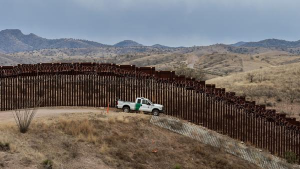 A Border Patrol officer guards the U.S.-Mexico border fence in Nogales, Ariz., in February. The Supreme Court on Friday said the Trump administration could continue with its plan to use military funds to build a wall along sections of the southern border.