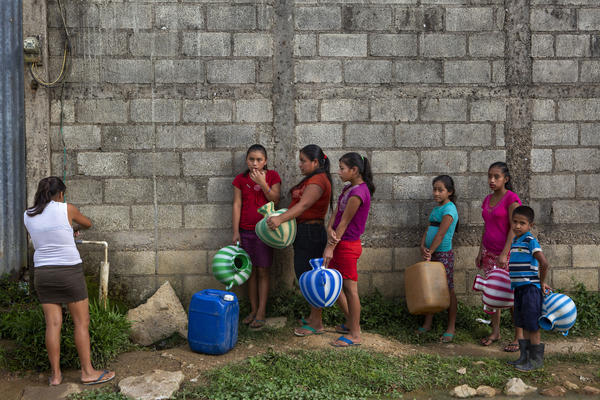 In this photo from May 2019 women wait to collect water in the village of El Tesoro, in Guatemala. Experts say climate change means more extreme weather, and Guatemala lacks the resources, and, critics say, political will to help impoverished areas.