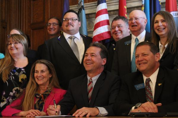 Gov. Steve Bullock is joined by Rep. Mary Caferro, a Democrat from Helena, and Rep. Ed Buttrey, a Republican from Great Falls, and other lawmakers for the signing of HB 658, May 9, 2019. The bill reauthorizes the state's Medicaid expansion program.