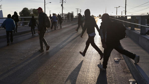 Migrants walk to the U.S.-Mexico border in Tijuana, Mexico, last week to make requests for political asylum.