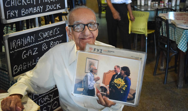 Boman Kohinoor, 97, has spent the past eight decades committed to his beloved Britannia & Co., one of Mumbai's last Parsi cafes. Here, he proudly holds up a photo of himself with two members of the British royal family: the Duke and Duchess of Cambridge, Prince William and the former Kate Middleton.