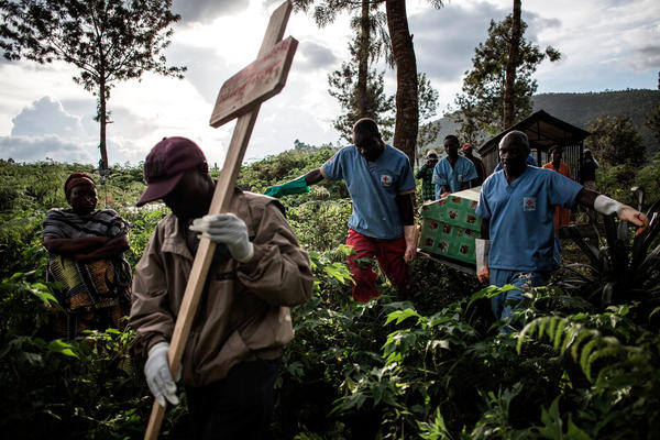 Health workers in Congo carry the coffins of Ebola victims to a burial site.