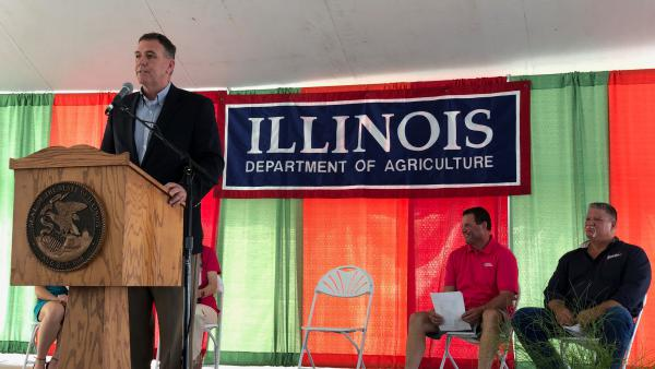 Illinois Department of Agriculture Director John Sullivan addresses a crowd at the Illinois State Fairgrounds on Aug. 1. At far right, fair manager Kevin Gordon.