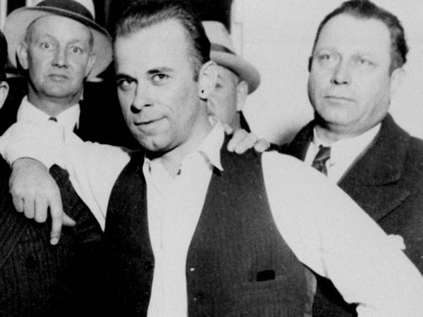 John Dillinger (center) strikes a jaunty pose after his capture in Crown Point, Ind., in February 1934. His niece and nephew hope to exhume the gangster's body to conduct forensic tests.