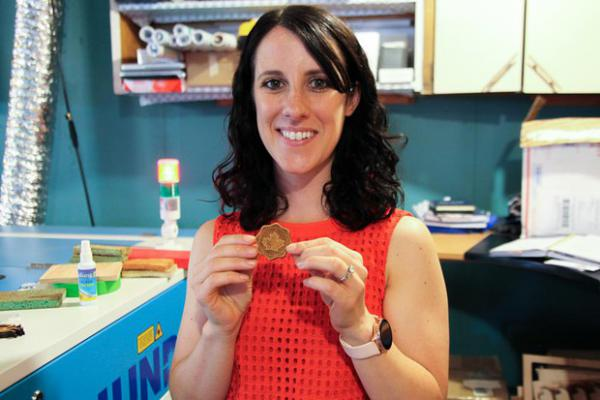 <p>Lindsey Brady holds one of the wooden tokens she makes at Toasted Maple, her business in The Dalles, Ore., July 18, 2019. As the owner of a growing small business, she wants to get sales tax right from the start.</p>