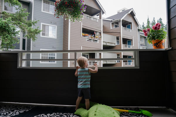 "Grigory Vodolazov's 3-year-old son peers into his family's apartment complex from their unit in Bellevue, Wash. The Vodolazov family is part of Creating Moves to Opportunity, a housing voucher experiment that uses incentives and counseling to encourage low-income families to move to what are called ""high opportunity"" areas."