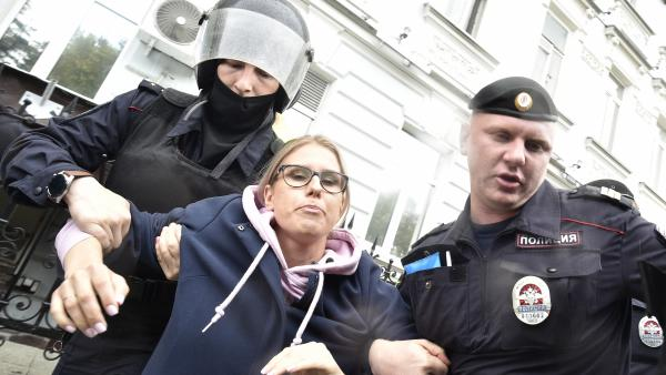 Police officers detain opposition candidate and lawyer Lyubov Sobol in Moscow on Saturday. Sobol was one of more than 600 arrested in Saturday's protests, according to an independent monitoring agency.