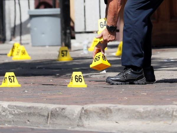 Authorities remove evidence markers at the scene of Sunday's mass shooting in Dayton, Ohio. Multiple people were killed in the second mass shooting in the U.S. in less than 24 hours, and the suspected shooter is also dead, police said.
