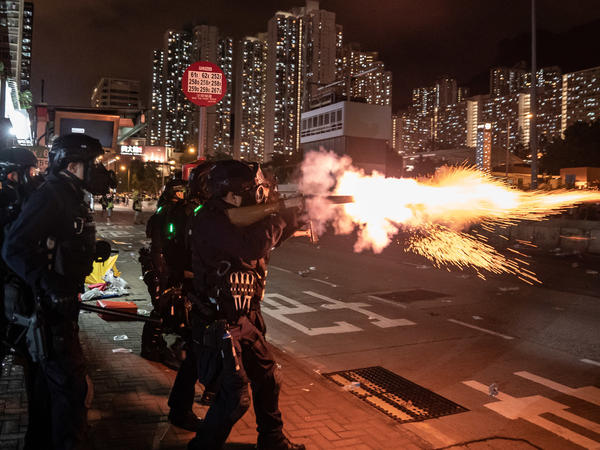 Riot police fire tear gas at protesters during a demonstration in Hong Kong's Wong Tai Sin District on Monday.