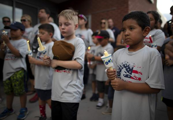 Children of a youth sports community participate in a vigil for the victims of Saturday's mass shooting in El Paso, Texas, Sunday, Aug. 4, 2019.