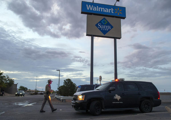 A Texas State Trooper walks back to his car while providing security outside the Walmart store in the aftermath of a mass shooting in El Paso, Texas.  (Andres Leighton/AP File Photo)