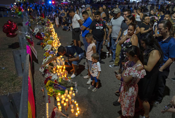 People gather at makeshift memorial for the victims of Saturday's mass shooting at a shopping complex in El Paso, Texas, Sunday, Aug. 4, 2019.