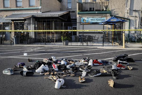 Shoes are piled outside the scene of a mass shooting near Ned Peppers bar, Sunday, Aug. 4, 2019, in Dayton, Ohio. Several people in Ohio have been killed in the second mass shooting in the U.S. in less than 24 hours.