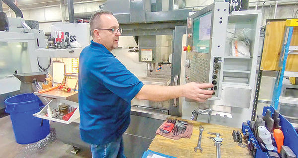 Kenneth Statton programs a CNC machine on the shop floor at MST Manufacturing in Claremore.