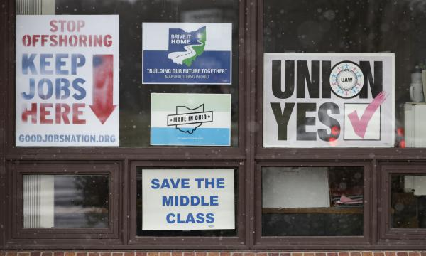 Signs hang from windows at the UAW Local 1112 union hall, Tuesday, Nov. 27, 2018, in Lordstown, Ohio.