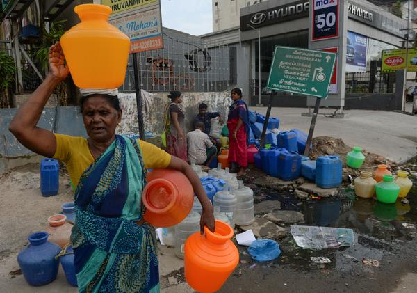 In this photo taken on June 20, Indian residents wait with plastic to get water at a distribution point in Chennai after reservoirs for the city ran dry.  The drought is the worst in living memory for the bustling capital of Tamil Nadu state.