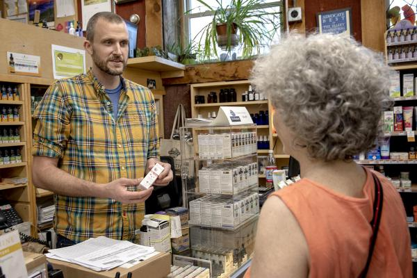 Nate Clifford, who owns Northampton's Cornucopia Natural Wellness Market with his wife, talks about a CBD product with a customer. (Robin Lubbock/WBUR)