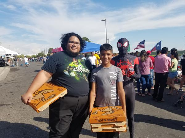 Juan Rivera and his two nephews, Bryant and Michael Rivera, brought pizzas to mourners at the Wal-Mart memorial. Michael wore a Spiderman outfit to bring smiles to children and families.