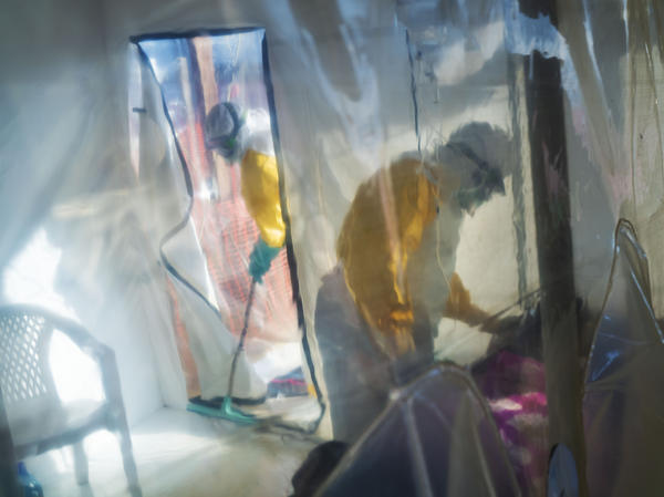 Health workers in protective suits tend to an Ebola victim kept in an isolation cube in Beni in the Democratic Republic of Congo.