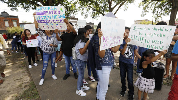 Children of mainly Latino immigrant parents hold signs in support of them and other individuals swept up during an immigration raid at a food processing plant in Mississippi.