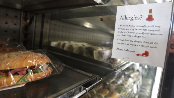 An allergy-warning notice is displayed next to food in a branch of Pret A Manger in central London. Pret A Manger is working to have full ingredient labeling in all its British shops by the end of 2019.