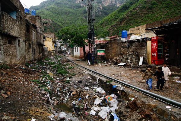 Boys play next to a riverbed filled with trash in Saidpur, a village near Islamabad, Pakistan.