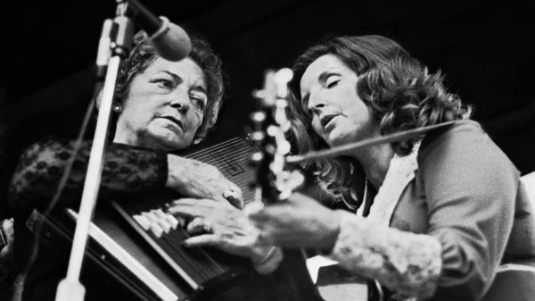 Maybelle Carter, playing her autoharp, performs with her daughter, Helen.