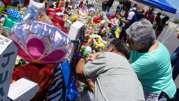 Humberto and Santos Vargas add a prayer to a white cross at the El Paso memorial. Each of the twenty-two crosses are in honor of those who lost thier lives on the Aug. 3 mass shooting.