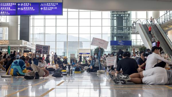 Demonstrators sit and lie on the arrival hall floor at Hong Kong International Airport in Hong Kong on Wednesday.