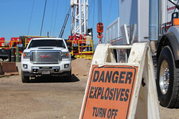 A sign at the edge of the orphaned well site warns of controlled explosions. Oil and gas workers take precautions by posting warning signs, wearing helmets and communicating regularly.