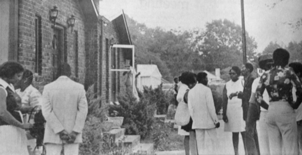 Mourners gather in front of the House of Hutchinson Funeral Home after flee- ing the chapel where the Reverend Willie Maxwell was shot to death during the funeral of Shirley Ann Ellington.