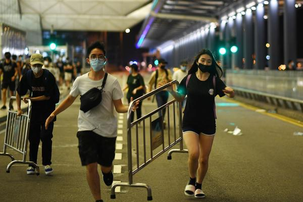 Pro-democracy protestors carry safety barriers to block the entrance to the airport terminals after a scuffle with police at Hong Kong's international airport.