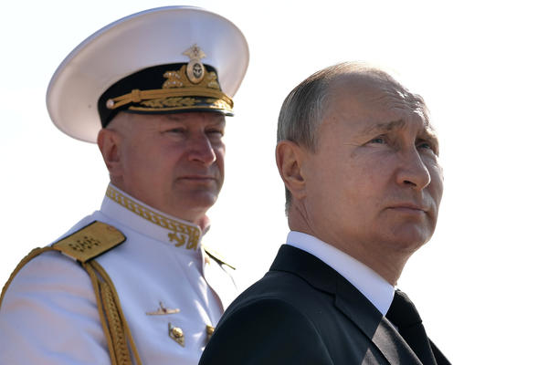 Russian President Vladimir Putin (R) and Russian Navy Commander-in-Chief Nikolai Yevmenov arrive to attend a parade of the Russian fleet. Officials in Russia originally said that the explosion took place on a boat.