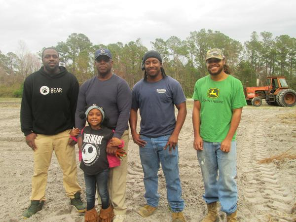 The Simmons are among the few African American farmers in North Carolina. Their story is featured in a new oral history project. From left to right Troy, Cleve (with granddaughter), Justin and Brian Simmons.