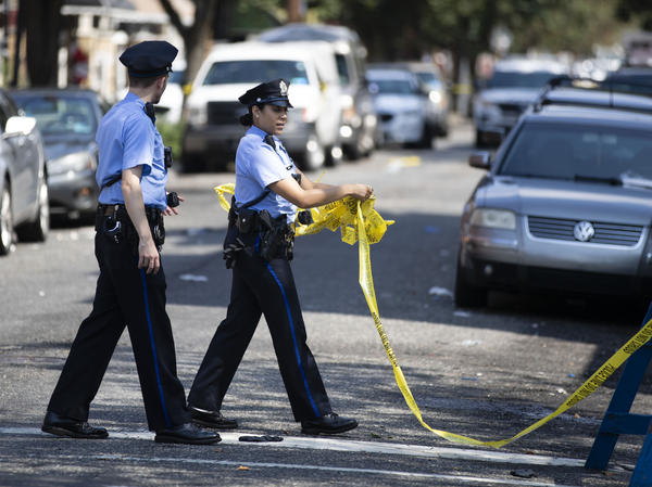 Officers remove tape Thursday from the scene of Wednesday's standoff with police in Philadelphia. The gunman, identified as Maurice Hill, wounded six police officers before surrendering early Thursday after a more than seven-hour standoff.