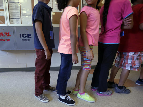 Detained immigrant children line up at a temporary home for immigrant women and children in Karnes City, Texas.